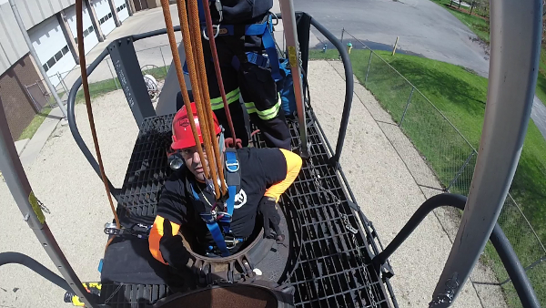 Industrial rescue students emerge from confined space during training