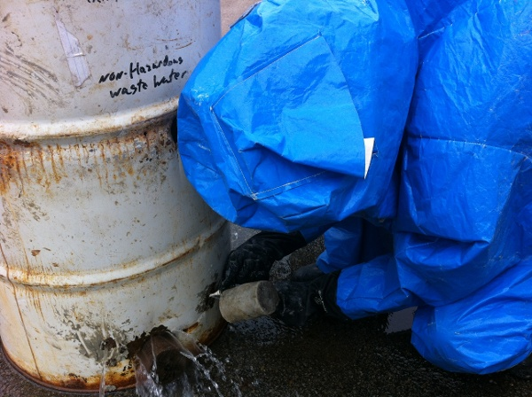 Student plugging a hole in barrel properly during hazmat training exercise
